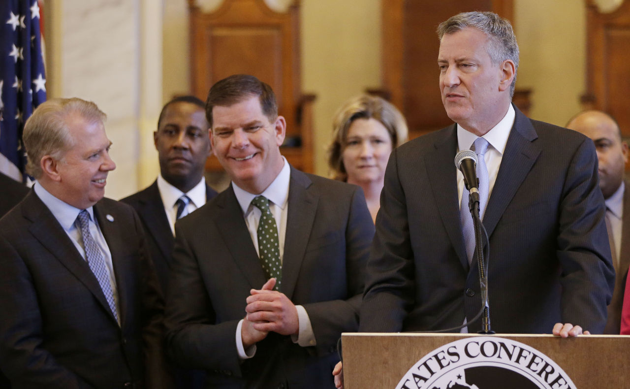 New York City Mayor Bill de Blasio addresses members of the media as Boston Mayor Marty Walsh, center, and Seattle Mayor Ed Murray, left, talk during a media availability after a U.S. Conference of Mayor's Cities of Opportunity Task Force session at historic Faneuil Hall Monday, March 23, 2015, in Boston. (AP)