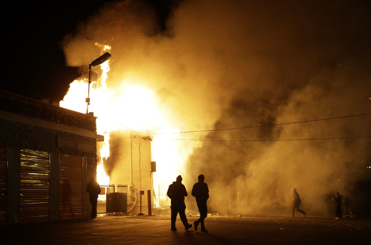 In this Monday Nov. 24, 2014 file photo, people walk away from a storage facility on fire after the grand jury decision was announced in Ferguson. (Jeff Roberson/AP)