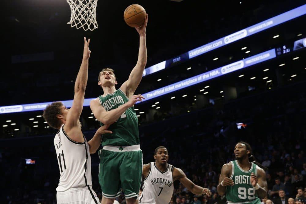 Celtics center Tyler Zeller (44) goes to the basket past Brooklyn Nets center Brook Lopez. (AP/Mary Altaffer)