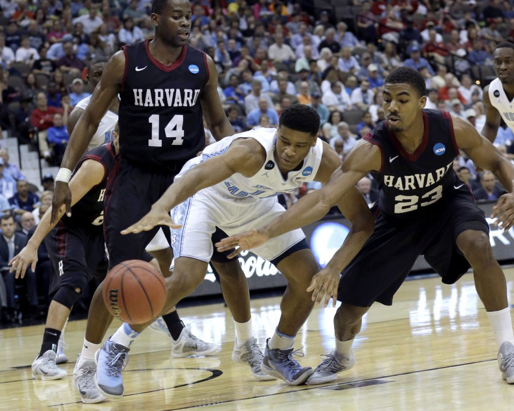 North Carolina forward Isaiah Hicks, center, and Harvard guard Wesley Saunders, right, reach for a loose ball in front of Harvard's Steve Moundou-Missi, left, during the second half of their game Thursday in Jacksonville, Fla. (John Raoux/AP)