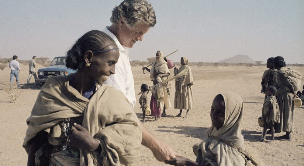 Sen. Edward Kennedy, center left, has a smile and a handshake for an unidentified young refugee in the Tuki-Baab famine refugee camp during a visit, Tuesday, Dec. 27, 1984, Tuki-Baab, Eastern Sudan. (Robert Dear/AP)