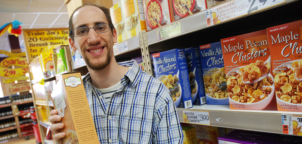 Brian Friedland, a composer who puts text from product packaging to music, scours the cereal aisle at a Trader Joe's. (Andrea Shea/WBUR)