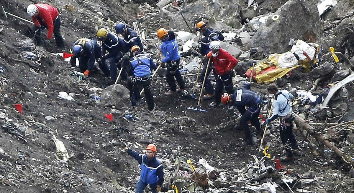 """Tom LeCompte: """"Who's going to land the plane if things go wrong? We already ride on trains without engineers and are preparing for driverless cars. Why not pilotless airliners?"""" Pictured: Rescue workers work on debris of the Germanwings jet at the crash site near Seyne-les-Alpes, France, Thursday, March 26, 2015. The co-pilot of the Germanwings jet barricaded himself in the cockpit and """"intentionally"""" rammed the plane full speed into the French Alps, ignoring the captain's frantic pounding on the cockpit door and the screams of terror from passengers, a prosecutor said Thursday. In a split second, he killed all 150 people aboard the plane. (Laurent Cipriani/AP)"""