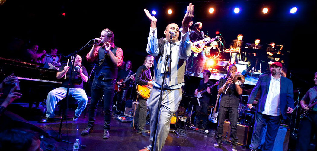 """Glen David Andrews claps at the mic during the 2013 """"SuperGroup"""" concert. Woody Giessmann sits at the piano at the left. (Michael Sparks Keegan)"""