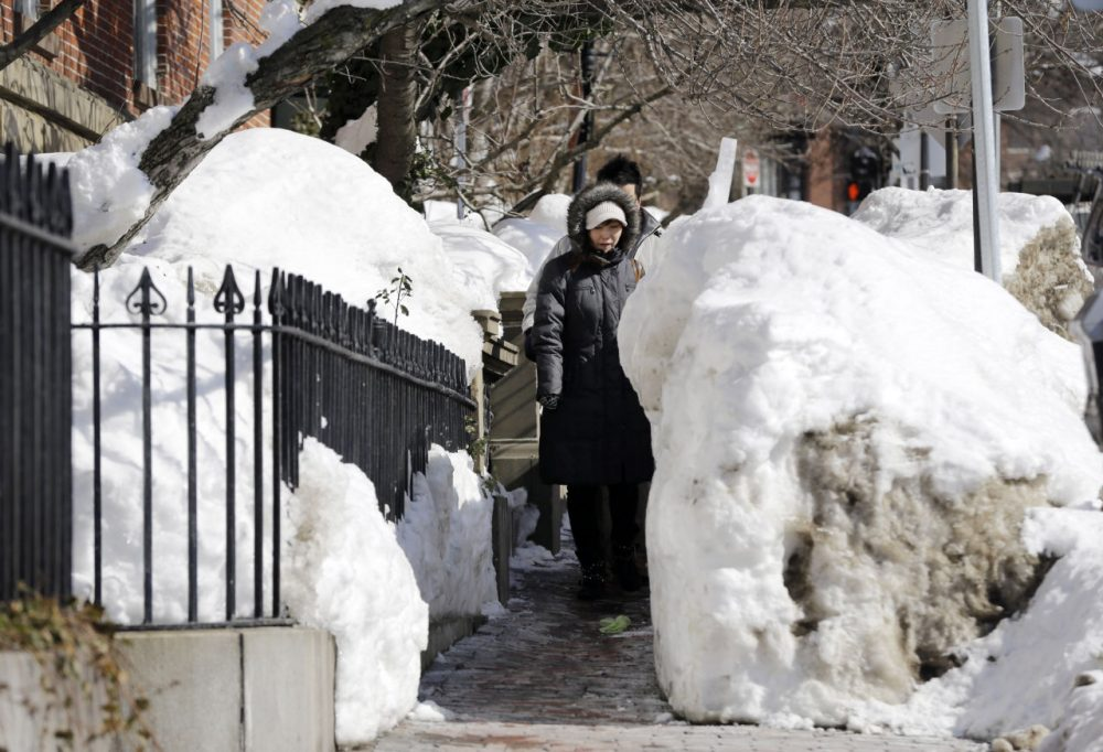 Pedestrians walk single file through snow banks on a Beacon Street sidewalk in Boston last month. (Elise Amendola/AP)