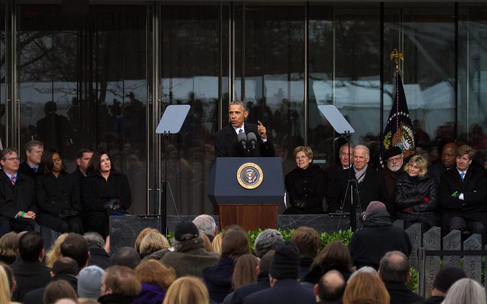 Surrounded by Kennedys and other politicians, President Obama speaks at the dedication of the Edward M. Kennedy Institute for the United States Senate in Boston on Monday. (Jesse Costa/WBUR)