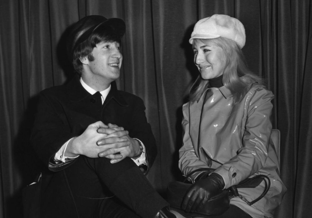 Singer and songwriter John Lennon (1940 - 1980), of The Beatles, with his wife Cynthia, wait for a flight to New York from London Airport, Feb. 7, 1964. (Keystone/Getty Images)