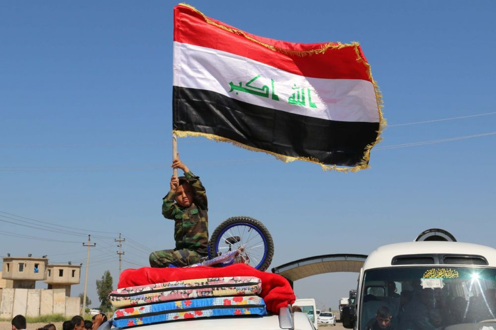 An Iraqi child waves his national flag as displaced families leave Kirkuk on April 2, 2015, to go back to the cities of Tikrit, Samara and al-Alam after they were retaken by security forces and pro-government fighters from the Islamic State group. (Marwan Ibrahim/AFP/Getty Images)