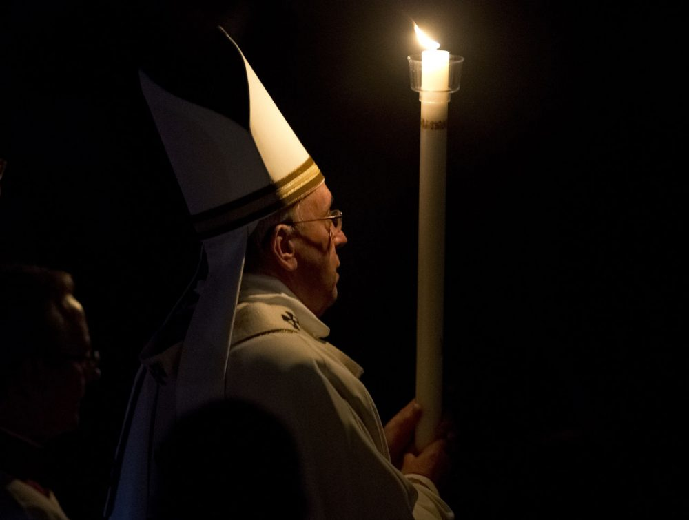 Pope Francis holds a white candle as he arrives for an Easter vigil service, in St. Peter's Basilica, at the Vatican, Saturday, April 4, 2015. (AP Photo/Andrew Medichini)