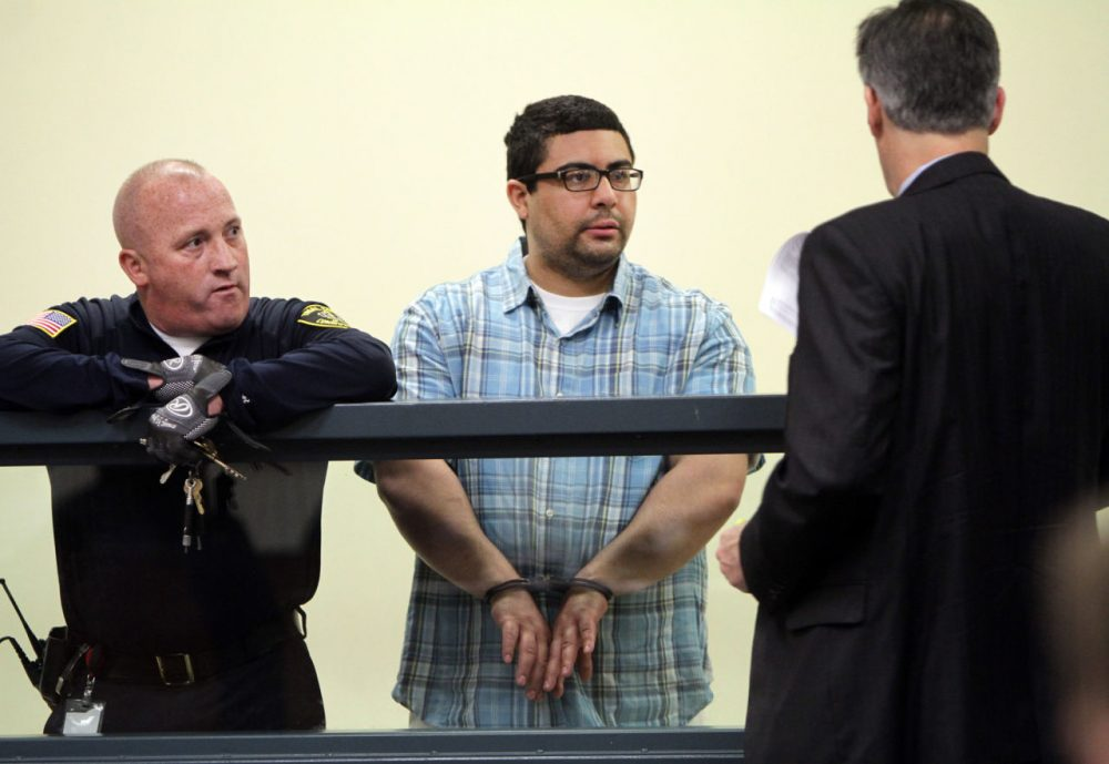 Carlos Colina, center, speaks with his attorney John Cunha, Jr., right, during his arraignment Monday. (Chitose Suzuki/The Boston Herald/ Pool)