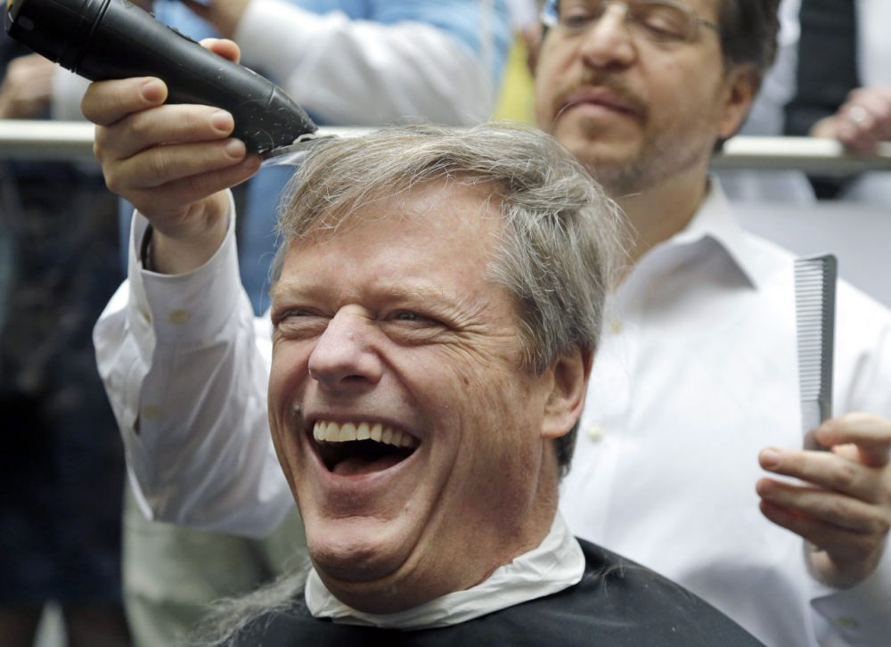 Gov. Charlie Baker reacts as he gets a buzz cut during a fundraising drive at Granite Telecommunications in Quincy, Mass. (Elise Amendola/AP)