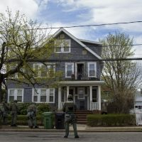 Heavily armed police officers do house to house searches in the neighborhoods of Watertown, Mass. Friday, April 19, 2013, as a massive search continued for one of two suspects in the Boston Marathon bombing. (Craig Ruttle/AP)