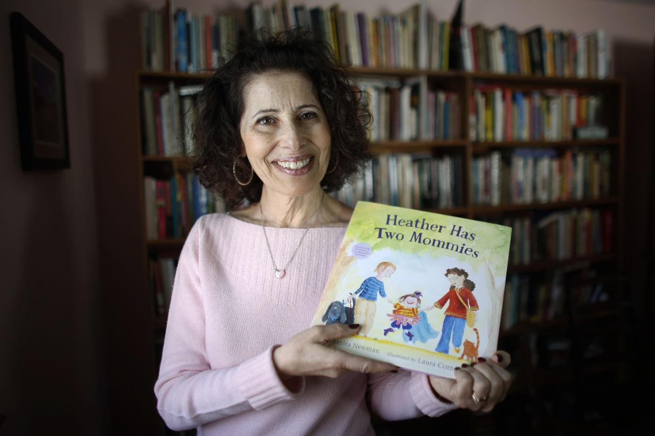 """Author Leslea Newman, of Holyoke, Mass., displays a copy of her book """"Heather Has Two Mommies,"""" in Holyoke, March 11, 2015. Newman, who wrote the original version of """"Heather Has Two Mommies,"""" 25 years ago, about a little girl named Heather and her two happy mommies, has updated the book with fresh illustrations from a new artist. (Steven Senne/AP)"""