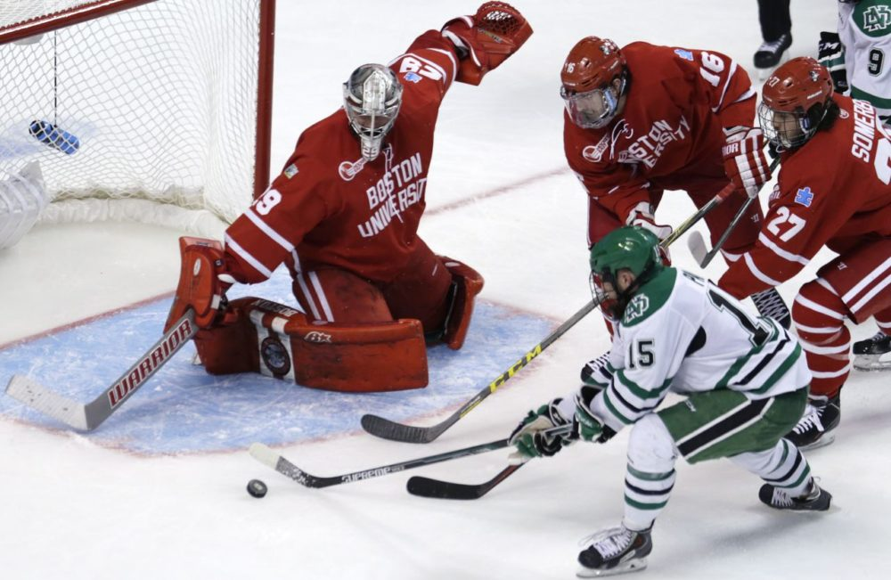 North Dakota forward Michael Parks (15) has his shot stopped by Boston University goalie Matt O'Connor during the second period of a semifinal at the NCAA men's Frozen Four hockey tournament in Boston Thursday. (Charles Krupa/AP)