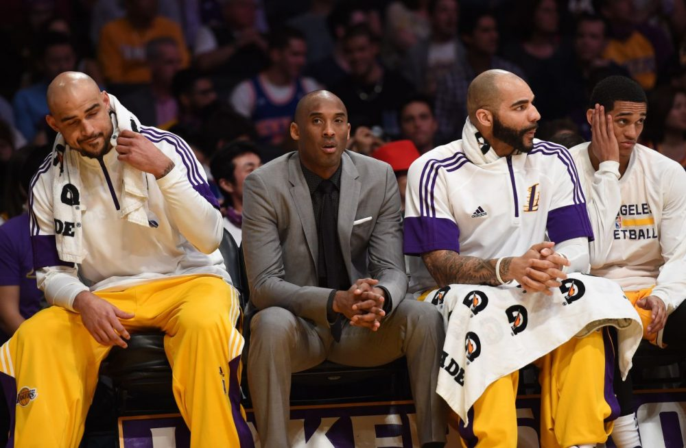 Injuries have kept some Lakers players -- like star Kobe Bryant (in suit) -- off the floor. Others are sitting for more suspicious reasons... (Mark Ralston/AFP/Getty Images)