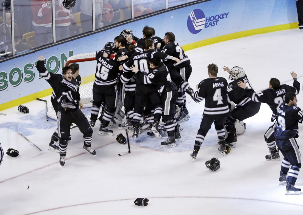 Providence players celebrate their 4-3 victory over Boston University in the NCAA men's Frozen Four hockey championship game in Boston, Saturday, April 11, 2015. (Elise Amendola/AP)