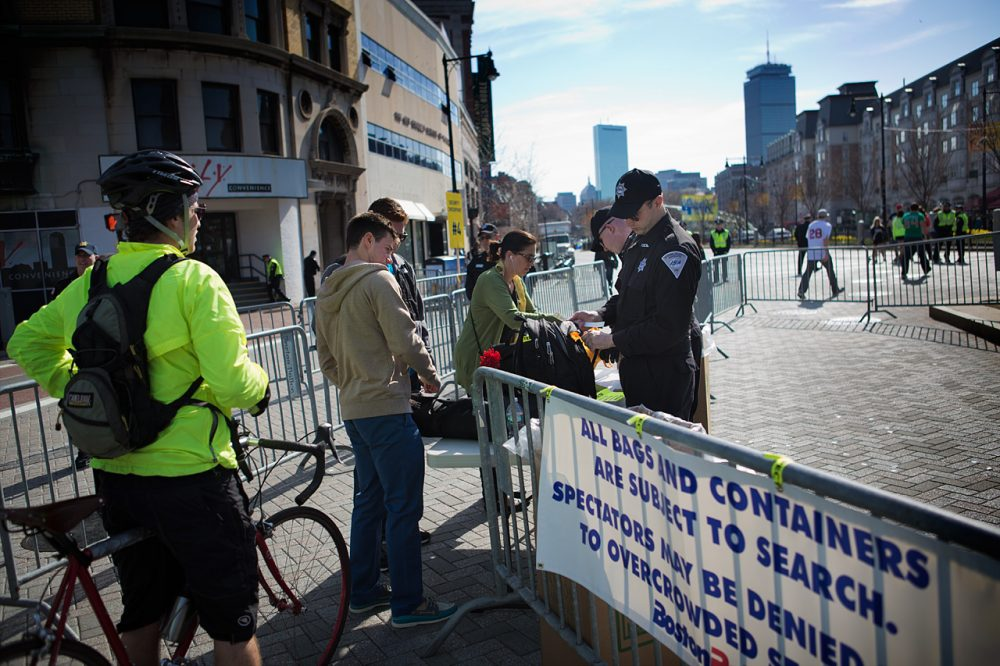 In this file photo from the 2014 Boston Marathon, Boston Police check bags along the marathon route near Kenmore Square. (Jesse Costa/WBUR)