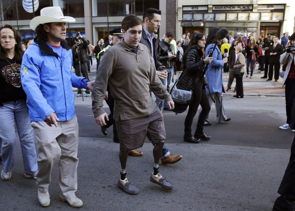 Boston Marathon survivor Jeff Bauman, right, walks past one of two blast sites with Carlos Arredondo, who helped save his life, near the finish line of the Boston Mararthon in Boston, Wednesday, April 15, 2015. Boston marked the second anniversary of the 2013 marathon bombings with a subdued remembrance that includes a moment of silence, the pealing of church bells and a call for kindness. (Charles Krupa/AP)