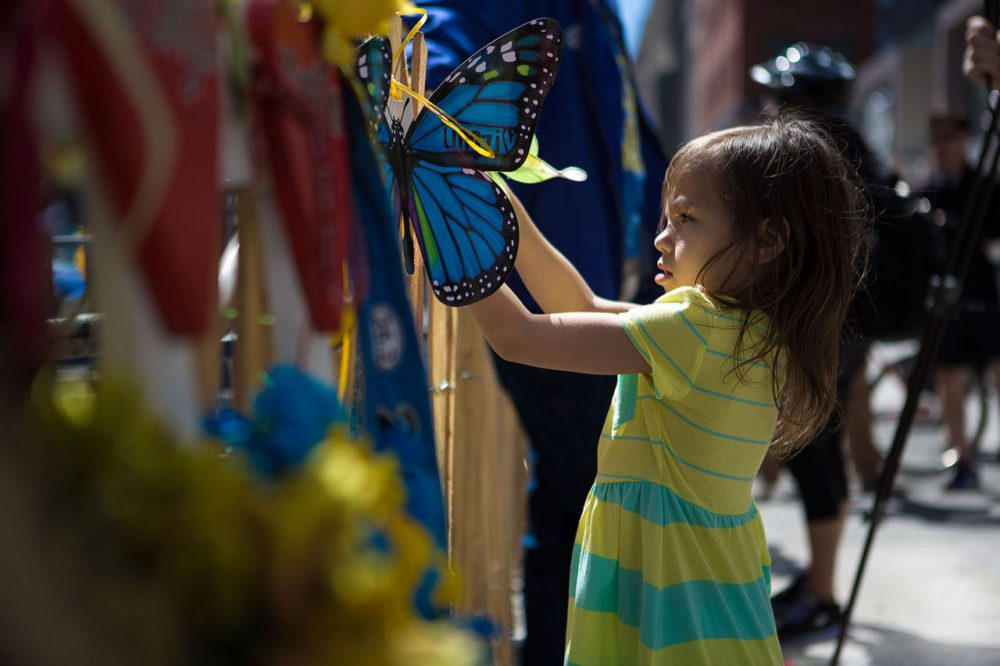 Six-year-old Jaslene Oyola, of Roxbury, hangs a butterfly on a memorial on Boylston Street Wednesday in honor of the Boston Marathon victims. (Jesse Costa/WBUR)