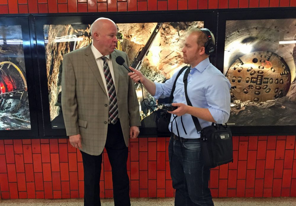 Here & Now's Jeremy Hobson interviews MTA Chairman Thomas Prendergast in front of an exhibit of photos of MTA heavy construction projects. (Adam Lisberg/MTA)