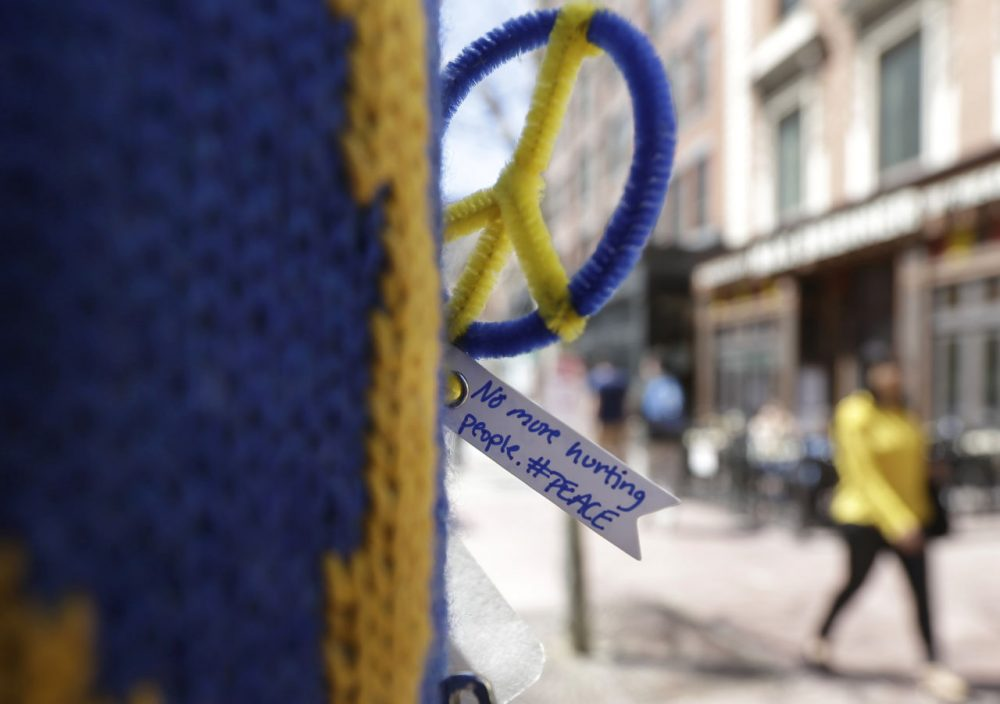 A peace symbol and a message are attached to a lamp post near one of two blast sites close to the finish line of the Boston Marathon, Wednesday, April 15, 2015. (Steven Senne/AP)