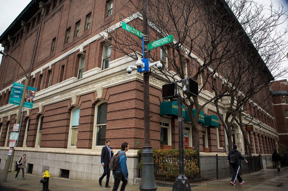 People pass by several surveillance cameras installed at the corner of Boylston and Hereford streets, near the Boston Marathon finish line. (Jesse Costa/WBUR)