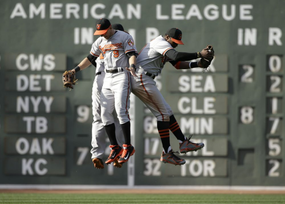 Baltimore Orioles Travis Snider, David Lough and Adam Jones jump in the air as they celebrate their 8-3 win over the Boston Red Sox on April 19, 2015, in Boston. (Steven Senne/AP)