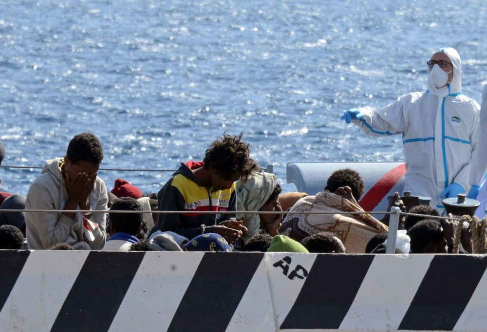 Migrants arrive in the port of Messina after a rescue operation at sea on April 18, 2015 in Sicily. A surge of migrants pouring into Europe from across the Mediterranean won't end before chaos in Libya is controlled, Italy's prime minister said yesterday, as the Vatican condemned a deadly clash between Muslim and Christian refugees on one boat. Italian authorities have rescued more than 11,000 migrants making the often deadly voyage from North Africa in the past six days, with hundreds more expected, the coastguard said. (Giovanni Isolino/AFP/Getty Images)