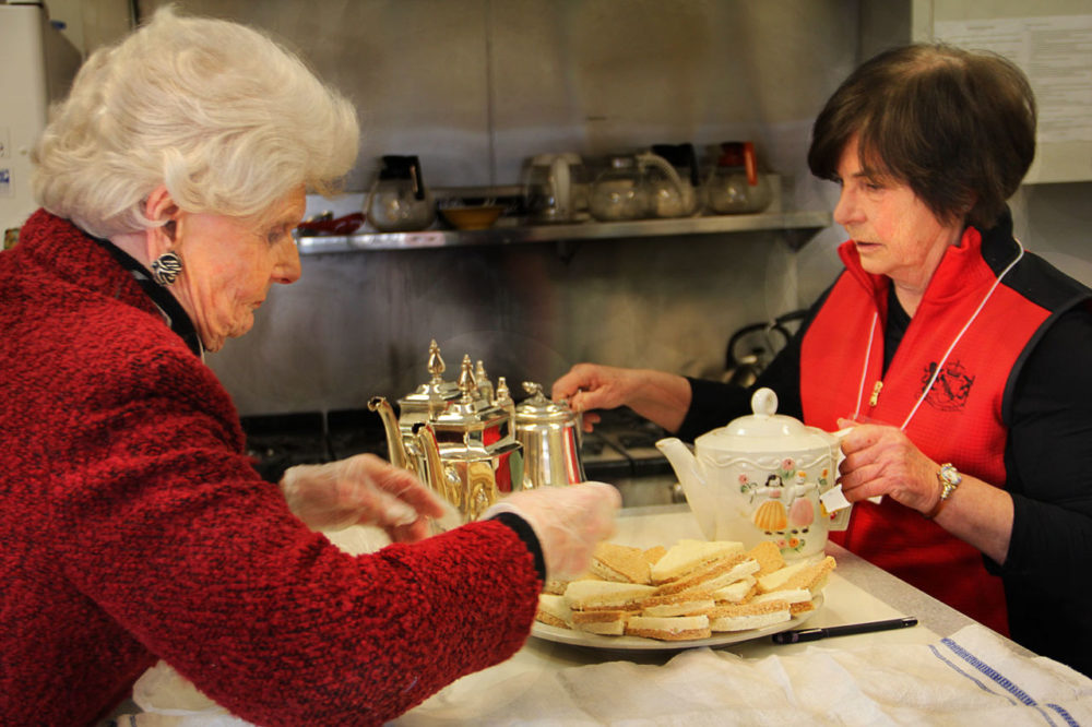 Tuesday Club members Alice Wilmont (left) and Karen Fulco (right) prepare tea and traditional tea sandwiches. (Shannon Dooling/WBUR)
