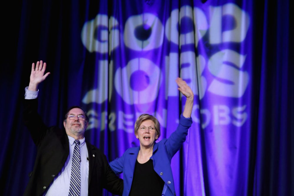 Sen. Elizabeth Warren (D-MA) is welcomed to the stage by United Steel Workers International President Leo Gerard (L) during the Good Jobs Green Jobs National Conference at the Washington Hilton April 13, 2015 in Washington, DC. Sponsored by a varied coalition including lightweight metals producer Alcoa, the United Steelworks union, the Sierra Club and various other labor, industry and telecommunications leaders, the conference promotes the use of efficient and renewable energy and cooperation in updating the country's energy infrastructure. (Chip Somodevilla/Getty Images)
