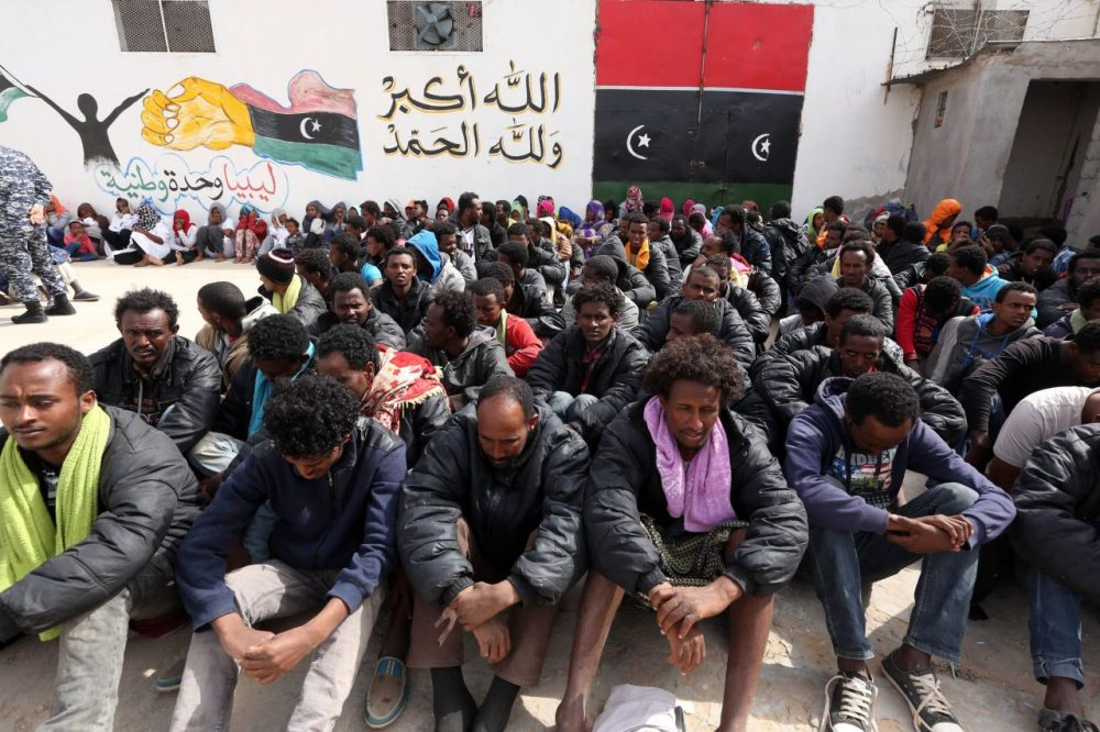 Migrants who were hoping to reach Europe by boat sit at Abu Salim detention centre for illegal migrants in the Libyan capital Tripoli on April 21, 2015, after they were detained at a Libyan port as they waited inside a boat to cross the Mediterranean Sea, according to Libyan security forces. (Mahmud Turkia/AFP/Getty Images)