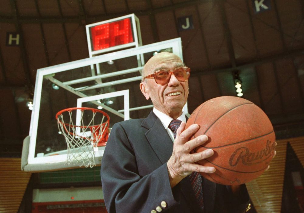 The late Danny Biasone, an innovator of the 24-second shot clock for professional basketball, is shown in this March 8, 1992 photograph at a gym at Syracuse University in Syracuse, N.Y. Behind him is a modern shot clock. Biasone and other National Basketball Association owners met in Syracuse in 1954 and tested the 24-second clock at a basketball game in a local school. That decaying school now is reaching out to the NBA for a donation.  (Michael Okoniewski/AP)
