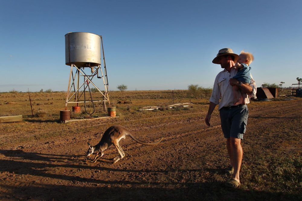Nic Walker carries his son Tasman in his arms during a daily afternoon walk at his property 'Rio Station' on March 20, 2014 in Longreach, Australia. Queensland, Australia's second-largest state, is currently suffering from its widest spread drought on record. Almost 80 percent of the region is now declared affected. The Australian government recently approved an emergency drought relief package of A$320m, of which at least A$280m is allocated for loans to assist eligible farm businesses to recover. (Lisa Maree Williams/Getty Images)