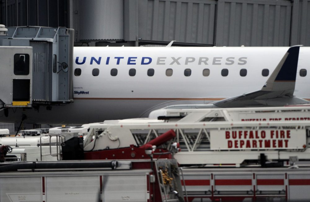 """Emergency vehicles surround a SkyWest Airlines plane, operating as United Express, that made an emergency landing at Buffalo Niagara International Airport, Wednesday, April 22, 2015, in Cheektowaga, N.Y. A SkyWest spokeswoman said one passenger aboard Flight 5622, lost consciousness and the pilots rapidly descended """"out of an abundance of caution."""" (Gary Wiepert/AP)"""