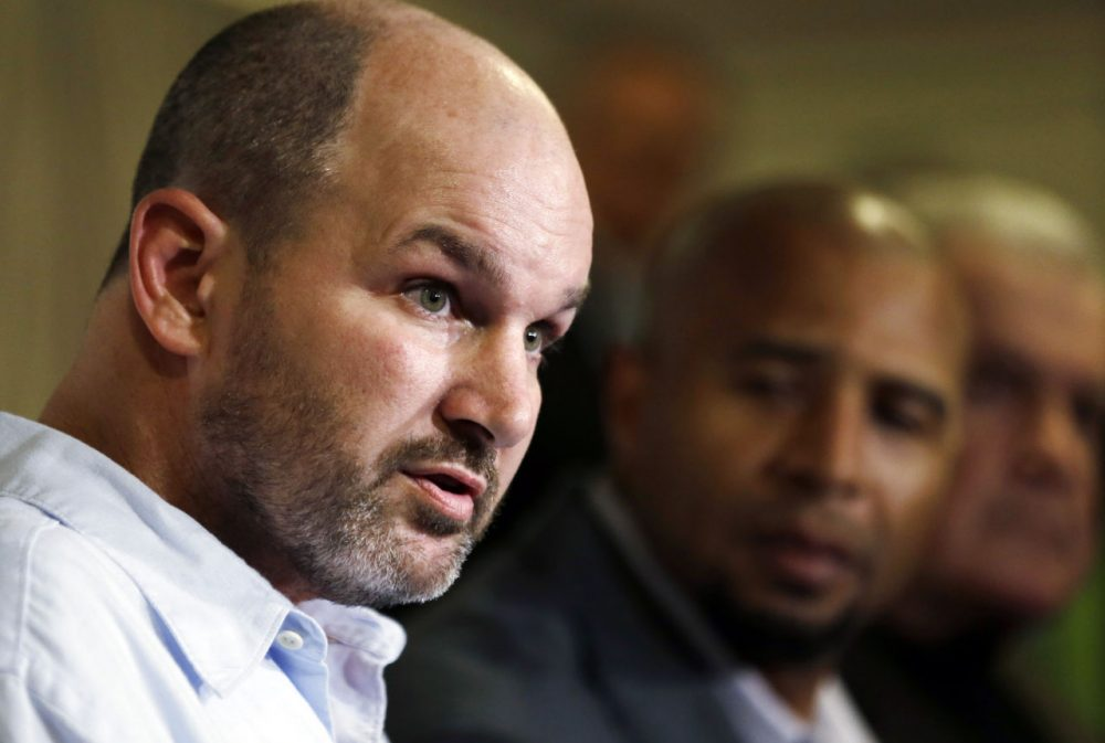 Former NFL player Kevin Turner speaks during a news conference in Philadelphia on April 9, 2013. As former players Dorsey Levens, center, and Bill Bergey listen. The NFL agreed Wednesday, June 25, 2014, to remove a $675 million cap on damages from thousands of concussion-related claims after a federal judge questioned whether there would be enough money to cover as many as 20,000 retired players. The plaintiffs include Kevin Turner, who played for the Philadelphia Eagles and New England Patriots and is now battling ALS. (Matt Rourke/AP)