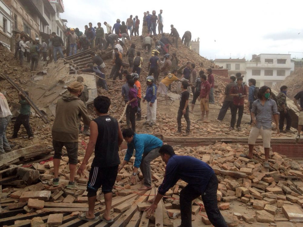 Volunteers help with rescue work at the site of a building that collapsed after an earthquake in Kathmandu, Nepal, Saturday, April 25, 2015. (AP Photo/ Niranjan Shrestha)