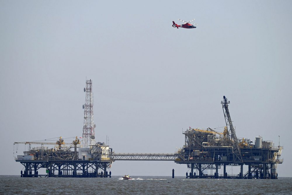 A U.S. Coast Guard helicopter flies over natural gas rigs in the waters of Mobile Bay off Dauphin Island, Ala., Sunday. Coast Guard crews are searching for five people missing in the water after a powerful storm capsized several sailboats participating in a regatta near Mobile Bay. (G.M. Andrews/AP)