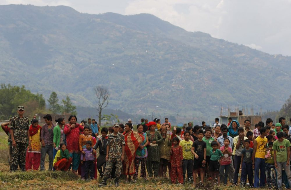 Nepalese villagers watch as relief material is brought in an Indian air force helicopter for victims of Saturday''s earthquake at Trishuli Bazar in Nepal, Monday. (Altaf Qadri/AP)