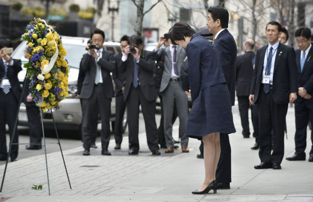 Japanese Prime Minister Shinzo Abe, center right, and his wife Akie bow after placing a wreath at the site of one of the 2013 Boston Marathon bomb blasts, on Monday. (Josh Reynolds/AP)
