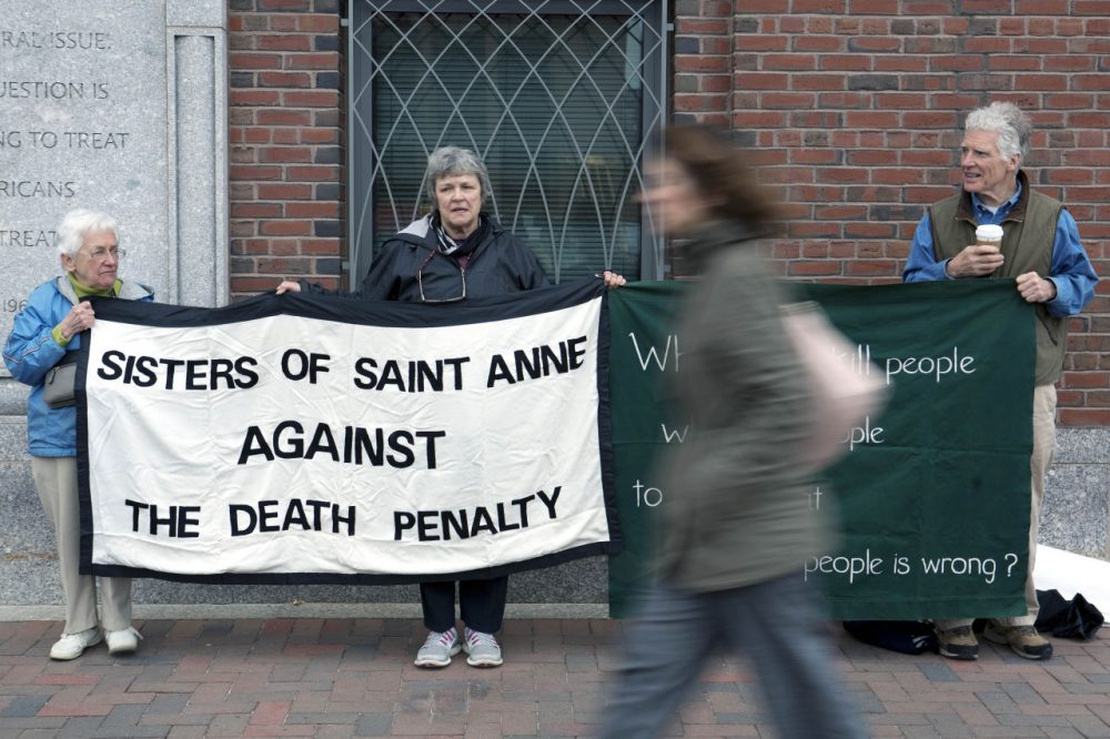 Death penalty protesters stand outside federal court Monday during the penalty phase of the federal trial of Dzhokhar Tsarnaev. (Justin Saglio/AP)