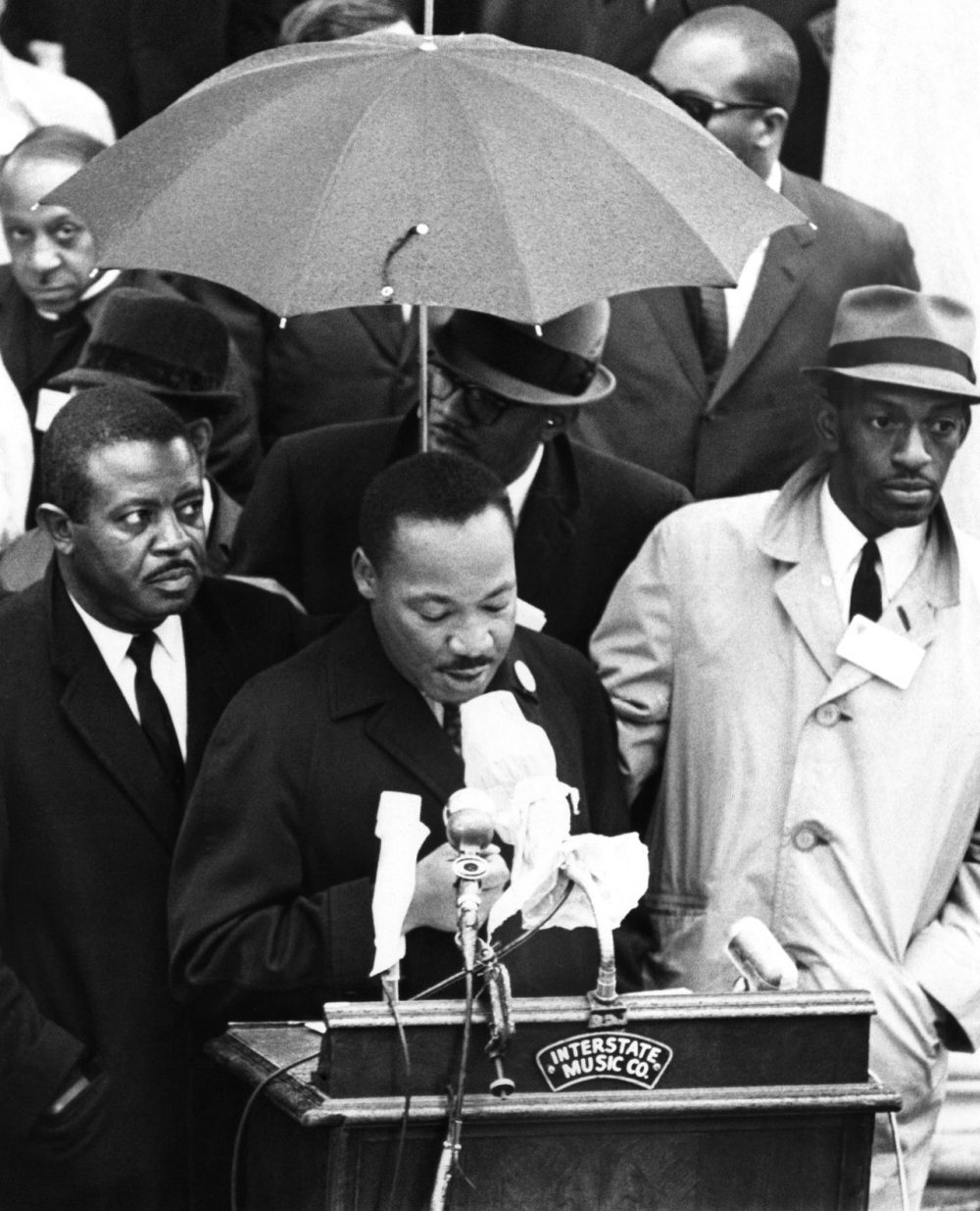 Dr. Martin Luther King Jr., protected by umbrella from rain, speaks to crowd on historic Boston Common, April 23, 1965. King led a civil rights march from the Roxbury section to the Common. He came to Boston, to lead the demonstration to protest segregation in schools, jobs and housing. (AP)