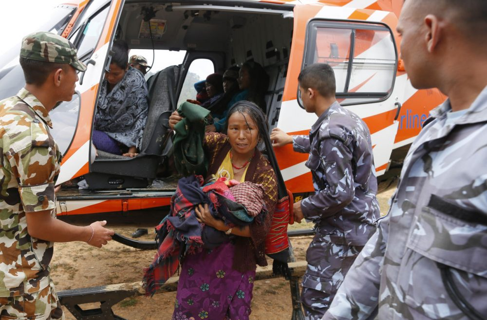 A mother injured in Saturday's massive earthquake carries her newborn child as she arrives by helicopter from the heavily-damaged Ranachour village at a landing zone in the town of Gorkha, Nepal, Tuesday, April 28, 2015. Helicopters crisscrossed the skies above the high mountains of Gorkha district on Tuesday near the epicenter of the weekend earthquake, ferrying the injured to clinics, and taking emergency supplies back to remote villages devastated by the disaster. (Wally Santana/AP)