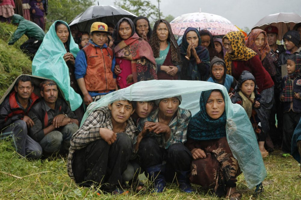 Villagers wait in the rain as an aid relief helicopter lands at their remote mountain village of Gumda, near the epicenter of Saturday's massive earthquake in the Gorkha District of Nepal on Wednesday. (Wally Santana/AP)