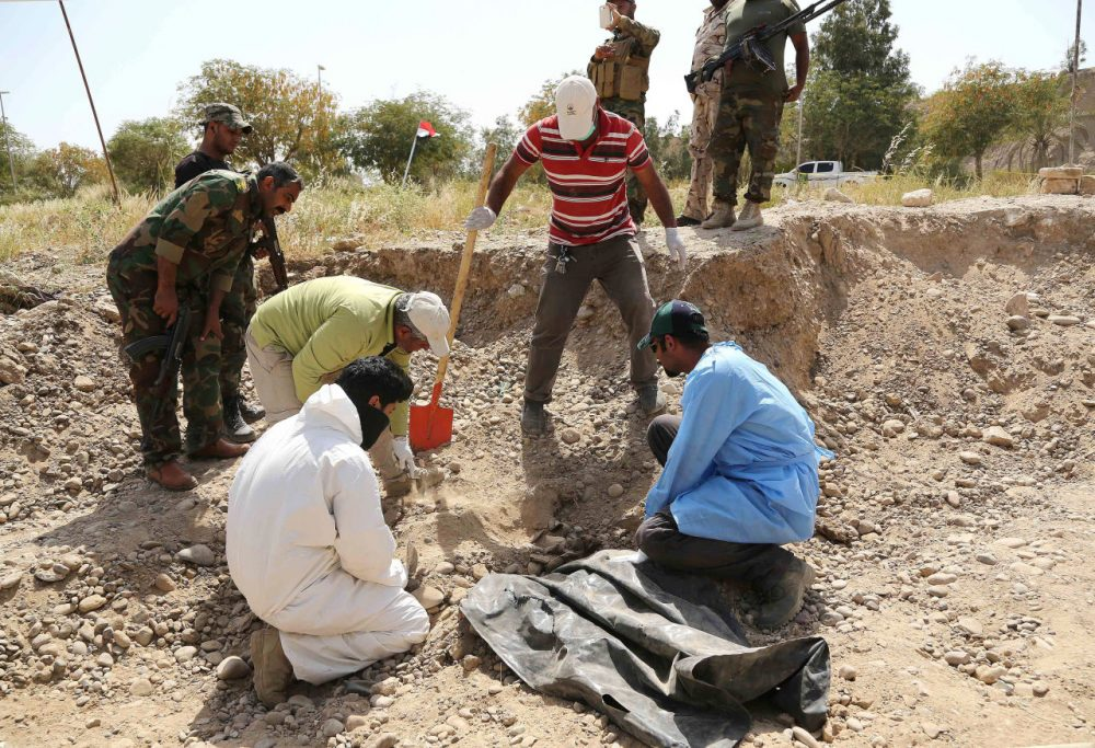 An Iraqi forensic team works at the site of a mass grave, believed to contain the bodies of Iraqi soldiers killed by Islamic State group militants when they overran Camp Speicher military base last June, in Tikrit, Iraq, 80 miles north of Baghdad, Thursday, April 9, 2015. (Karim Kadim/AP)
