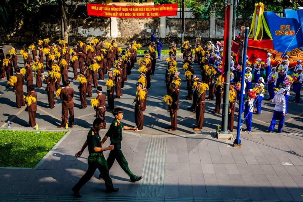 Parade marchers representing workers and farmers wait in formation for the Reunification Day parade to begin, Thursday in Ho Chi Minh City. (Quinn Ryan Mattingly for WBUR)