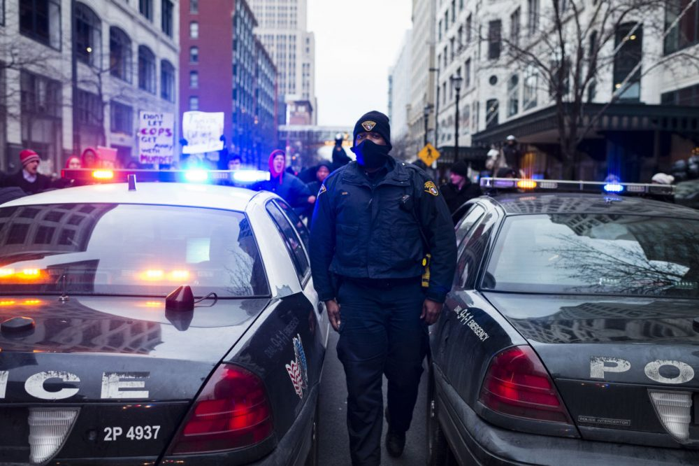 An unidentified Cleveland Police Officer walks between cars on Ontario Street December 21, 2014. Demonstrators  protesting the death of 12-year-old Tamir Rice locked arms to prevent police cruisers from passing. (Angelo Merendino/Getty Images)
