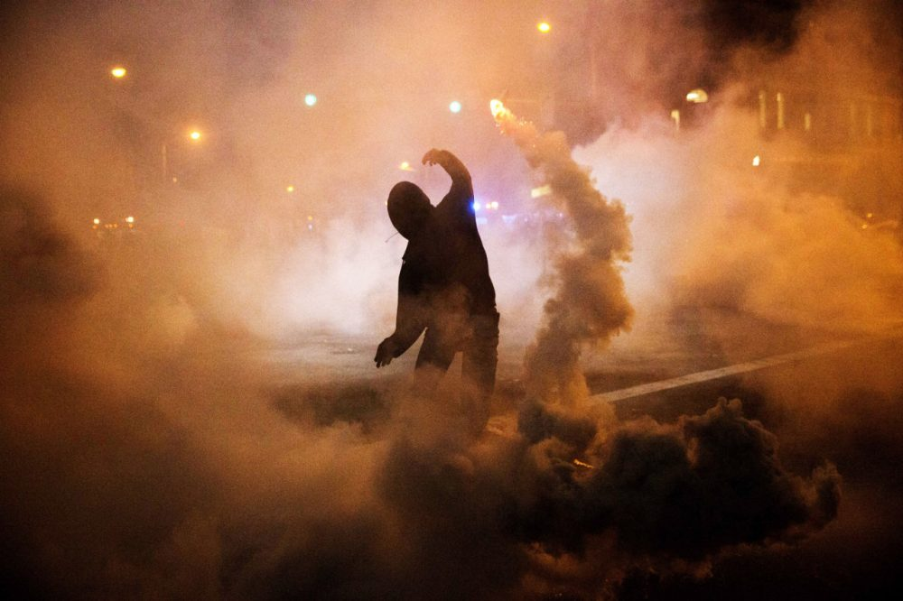 A protester throws a tear gas canister back toward riot police after a 10 p.m. curfew went into effect in the wake of Monday's riots following the funeral for Freddie Gray, Tuesday, April 28, 2015, in Baltimore. (David Goldman/AP)