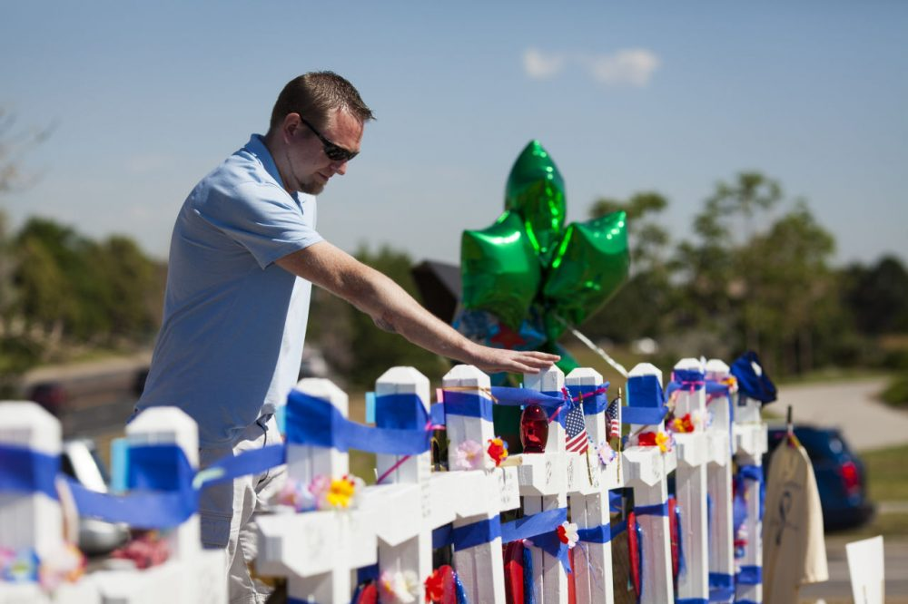 Joshua Nowlan, 32, visits the 12 crosses erected near the Aurora Municipal Building July 20, 2013 in Aurora, Colorado. A remembrance ceremony marks the one one-year anniversary of the Aurora Movie Theatre Shootings in which James Holmes killed 12 people and injured more than 50 during a mass shooting in 2012. (Dana Romanoff/Getty Images)