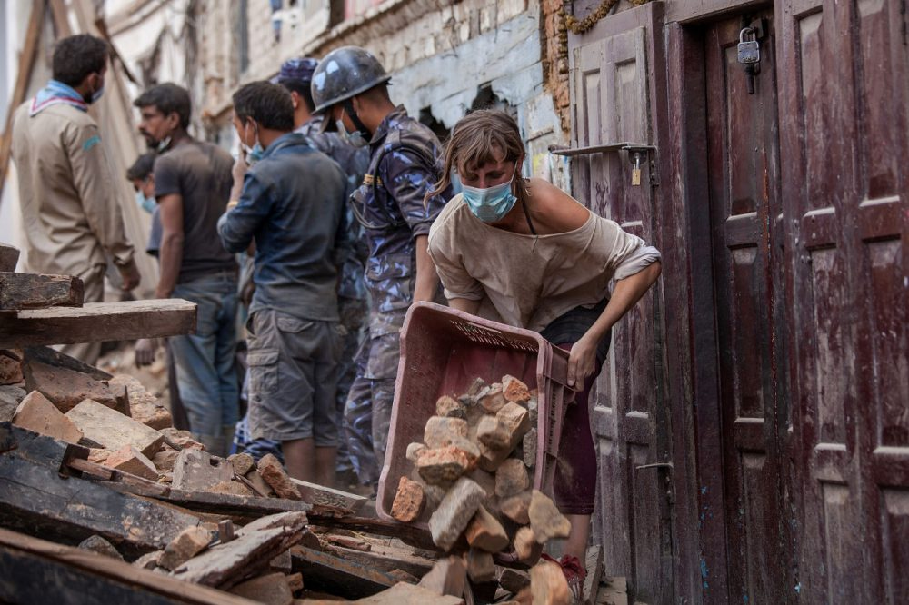 A foreign volunteer clears debris of a collapsed temple at Basantapur Durbar Square on April 27, 2015 in Kathmandu, Nepal. (Omar Havana/Getty Images)