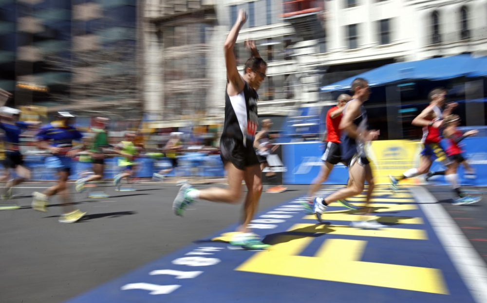 Runners make their way over the finish line in the 118th Boston Marathon, Monday, April 21, 2014. (Elise Amendola/AP)